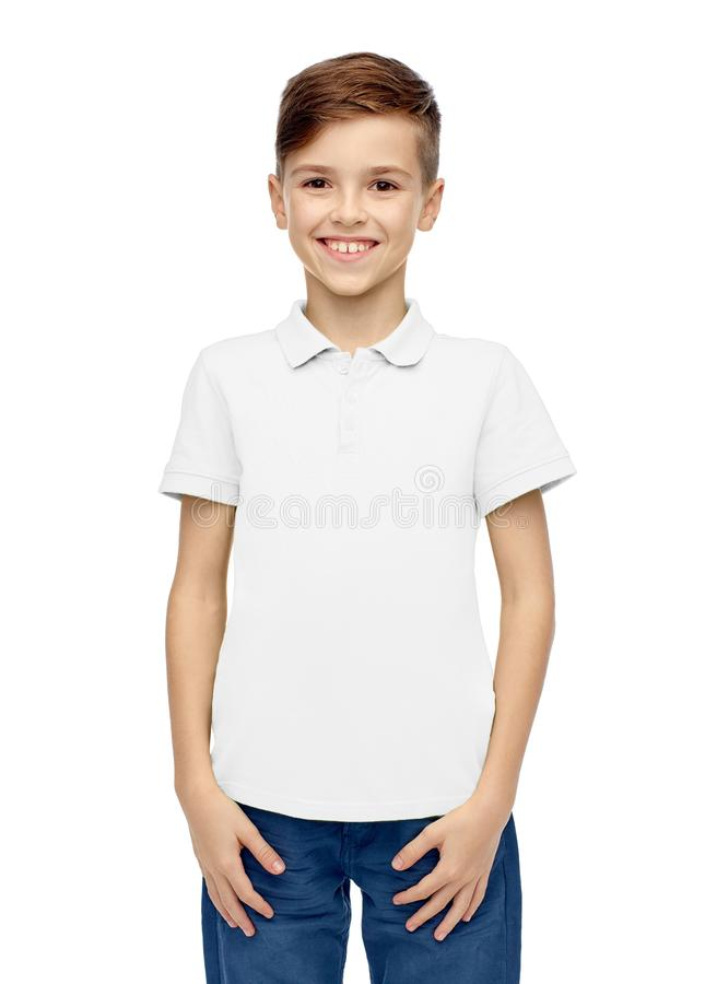 Happy boy in white blank polo t-shirt. Fashion and people concept - happy smiling boy in white blank polo t-shirt royalty free stock images