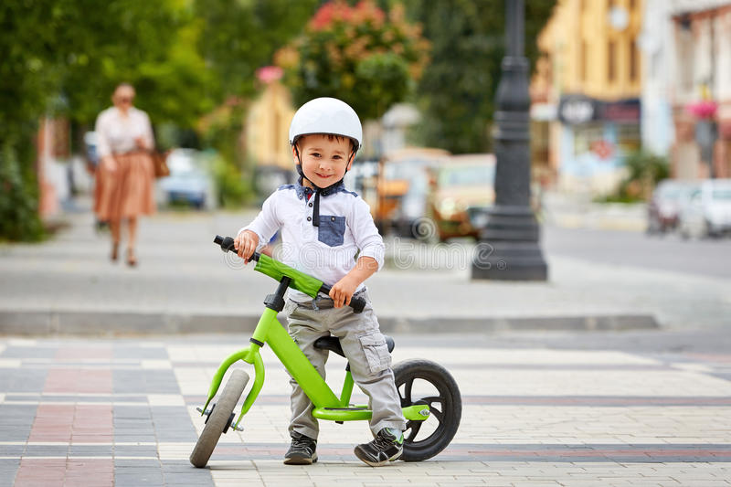 Happy boy in white helmet ride his first bike royalty free stock photos