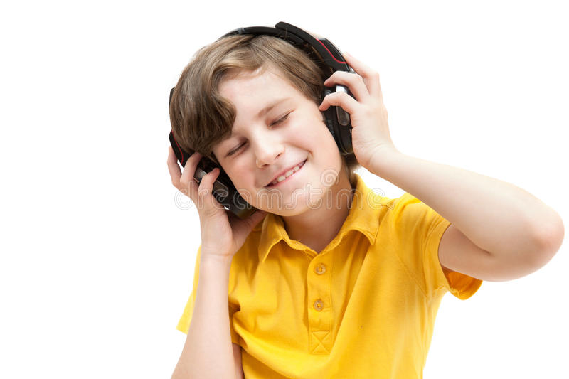 Happy boy in yellow t-shirt listens music with headphones. Happy boy listens music with headphones, isolated on white royalty free stock photo