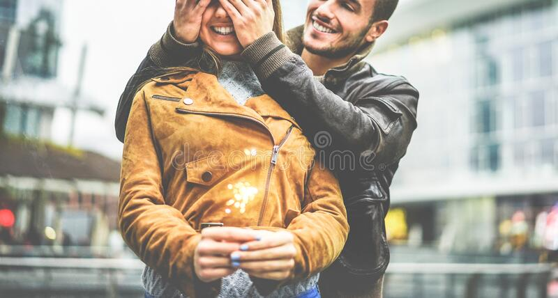 Happy boyfriend covering girlfriend eyes during winter holidays - Young woman making a wish holding firework - Love and winter. Happy boyfriend covering stock photography