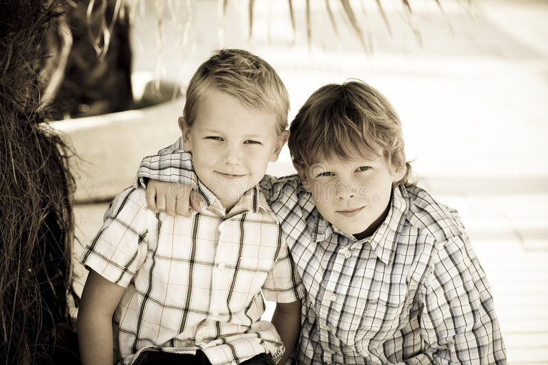 Happy boys. Happy young brothers sitting outside stock photography