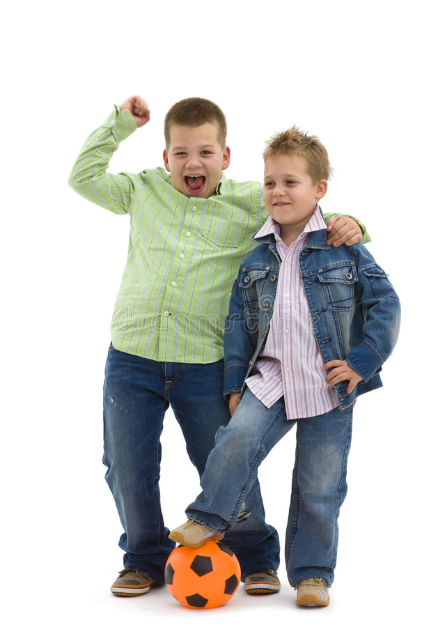 Happy boys with football. Happy young brothers wearing trendy jeans clothers posing togethers with football, on isolated white background royalty free stock images