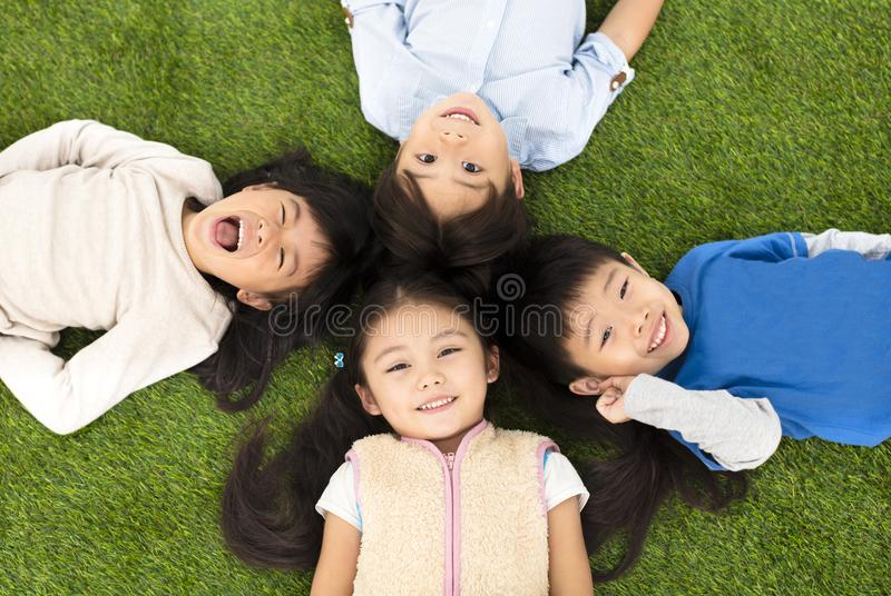 Boys and girls lying on green grass stock photos