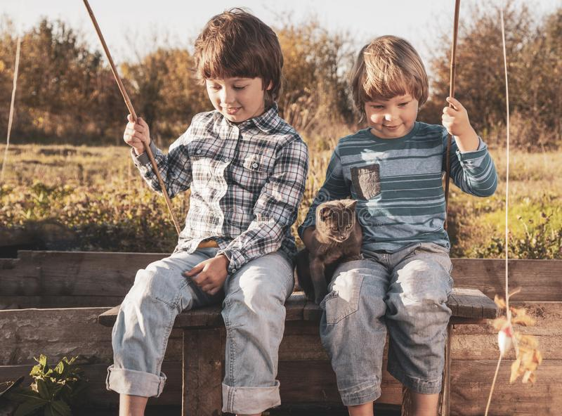 Happy boys go fishing on the river, Two children of the fisher with a fishing rod on the shore of lake stock photography