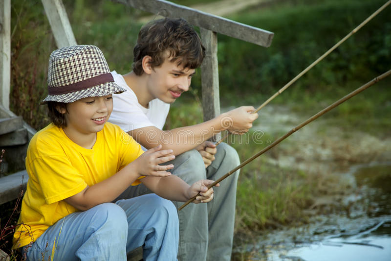 Happy boys go fishing on the river, Two children of the fisherman with a fishing rod on the shore of lake royalty free stock image