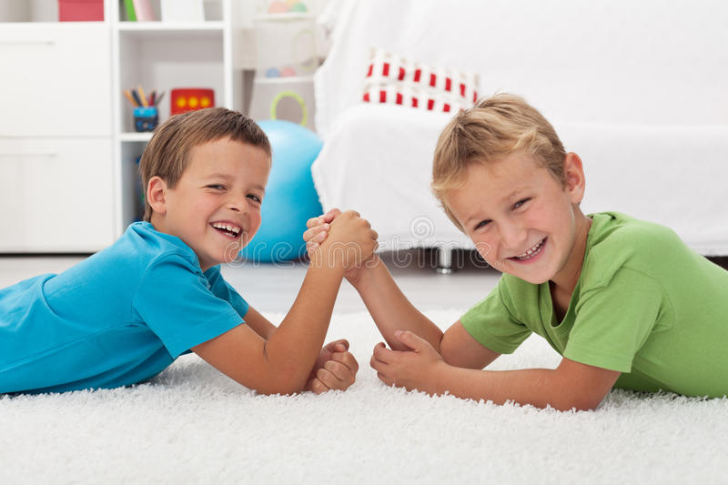 Happy boys laughing and arm wrestling. Happy kids laughing and arm wrestling - focus on the left boy stock photography
