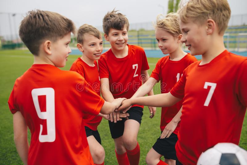 Children Football Soccer Team Standing Together in a Circle. Happy boys play team sport. Kids smiling in school sports team. Junior sports teamwork; kids put stock photo