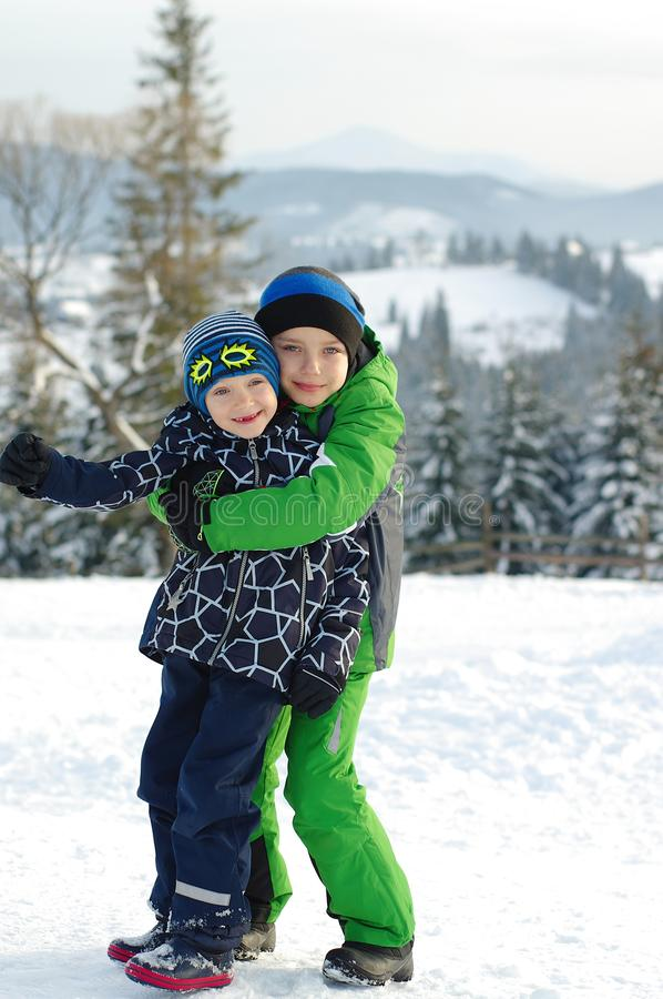 Happy boys playing on a winter walk in nature. Children jumping and having fun in winter park royalty free stock images