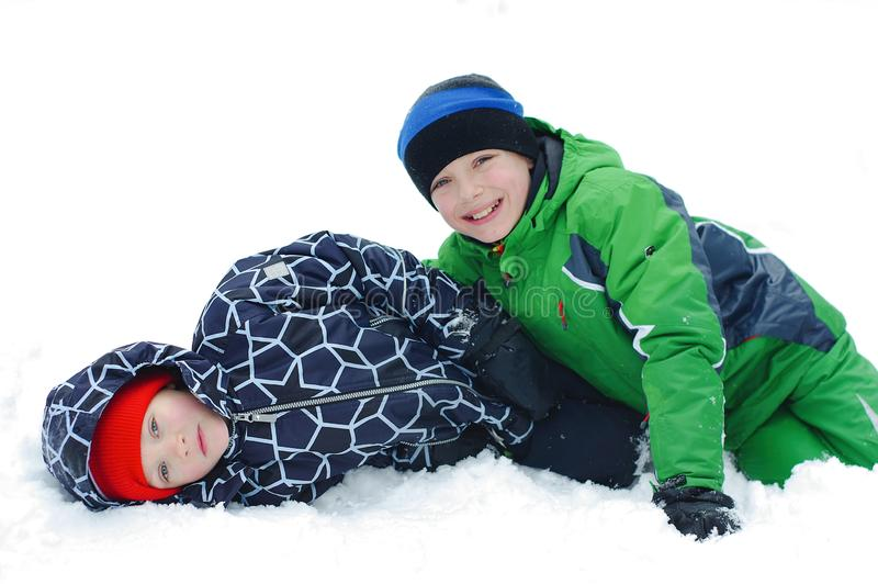 Happy boys playing on a winter walk in nature. Children jumping and having fun in winter park royalty free stock image