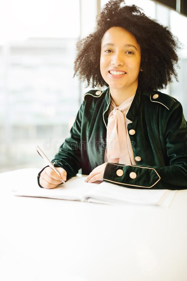Happy brazil latin student girl. In fashinable green jacket study royalty free stock photography