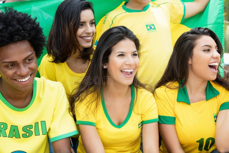 Happy brazilian soccer fans with flag at stadium. Happy brazilian soccer fans with jersey an flag at stadium royalty free stock photo