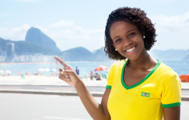 Happy brazilian sports fan pointing at Sugarloaf mountain. With Copacabana beach and ocean in the background stock photography