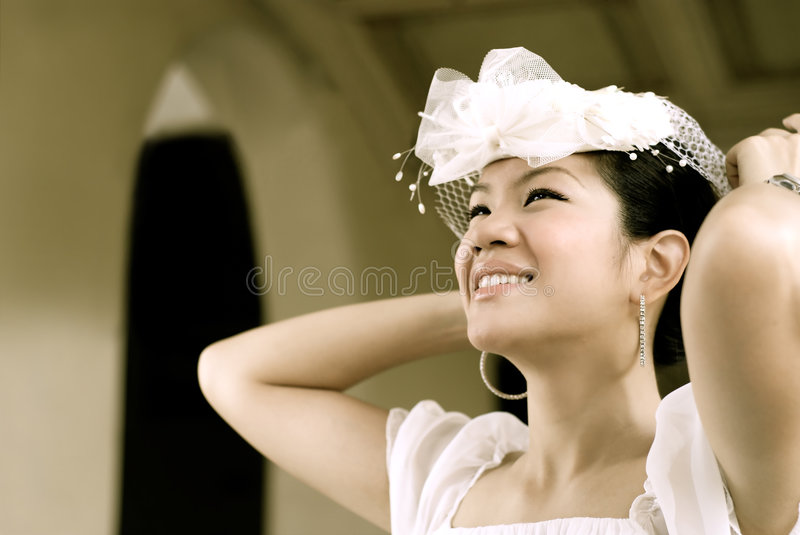 Happy bride. Portrait cute in white wedding wear , arm over head royalty free stock images