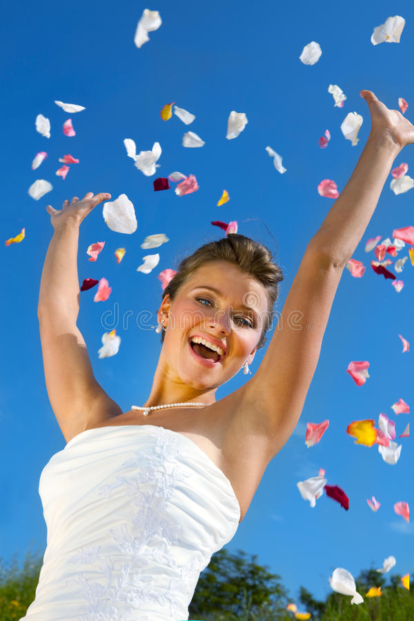 Happy Bride and Colorful Petals at the Blue Sky. Happy Beautiful Bride and Colorful Petals at the Blue Sky royalty free stock photos