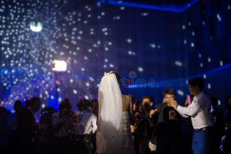 Happy bride dance at wedding party with guests and colour led lighting. royalty free stock photo
