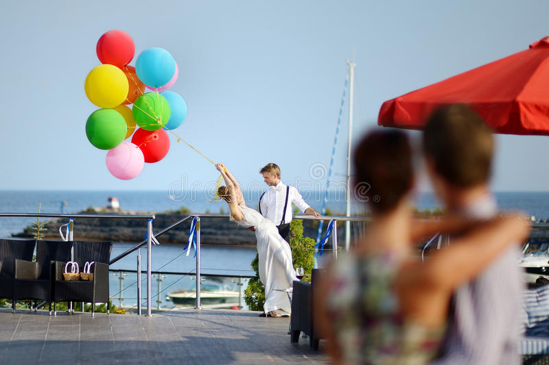 Happy bride and groom with balloons. Happy bride and groom with colorful balloons stock photo