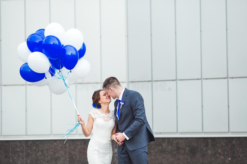 Happy bride and groom celebrating wedding day with balloons royalty free stock photo
