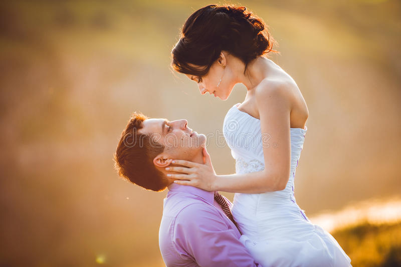 Happy bride and groom celebrating wedding day. Married couple in front of sunset. Toned image royalty free stock photo
