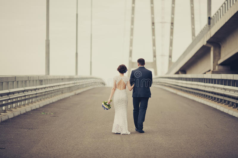 Happy bride and groom celebrating wedding day. Married couple going away on bridge. Long family life road concept. Toned stock photo