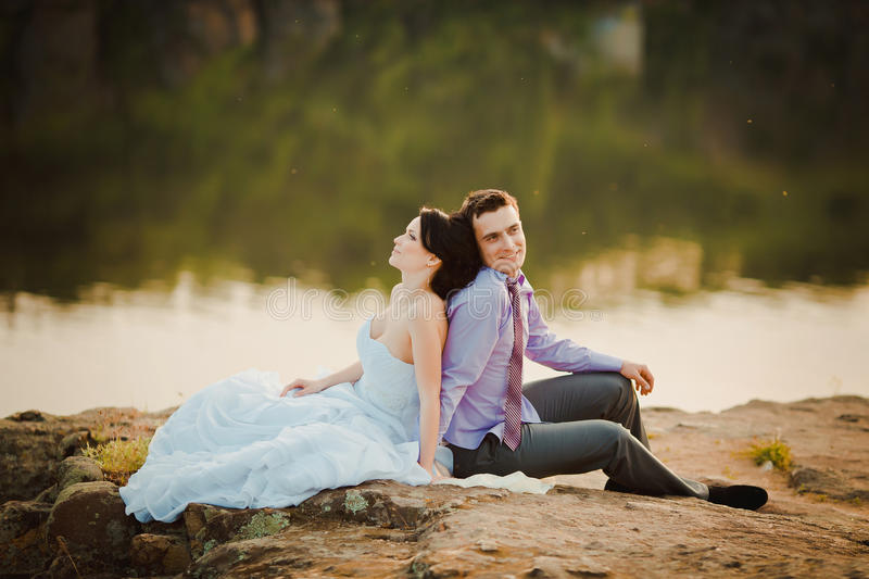 Happy bride and groom celebrating wedding day. Married couple sitting together royalty free stock photography