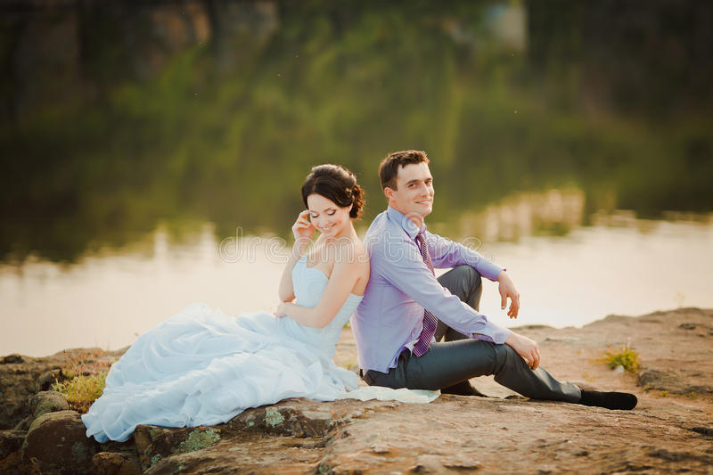 Happy bride and groom celebrating wedding day. Married couple sitting together royalty free stock photos