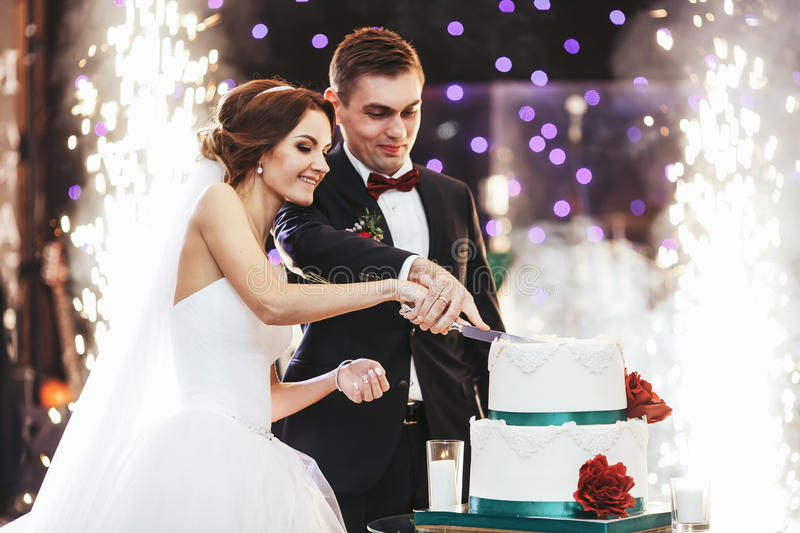 Happy bride and groom cut the wedding cake in the front of fireworks stock images