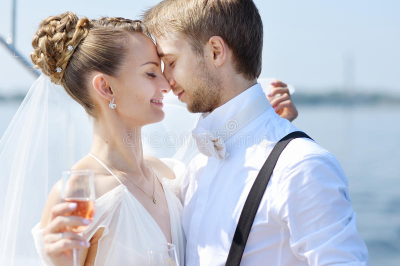 Happy bride and groom drinking champagne. On a yacht royalty free stock photos