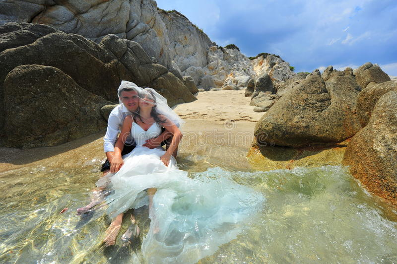 Happy bride and groom feeling great on honeymoon. Beautiful young couple in their wedding outfits on a tropical ebach