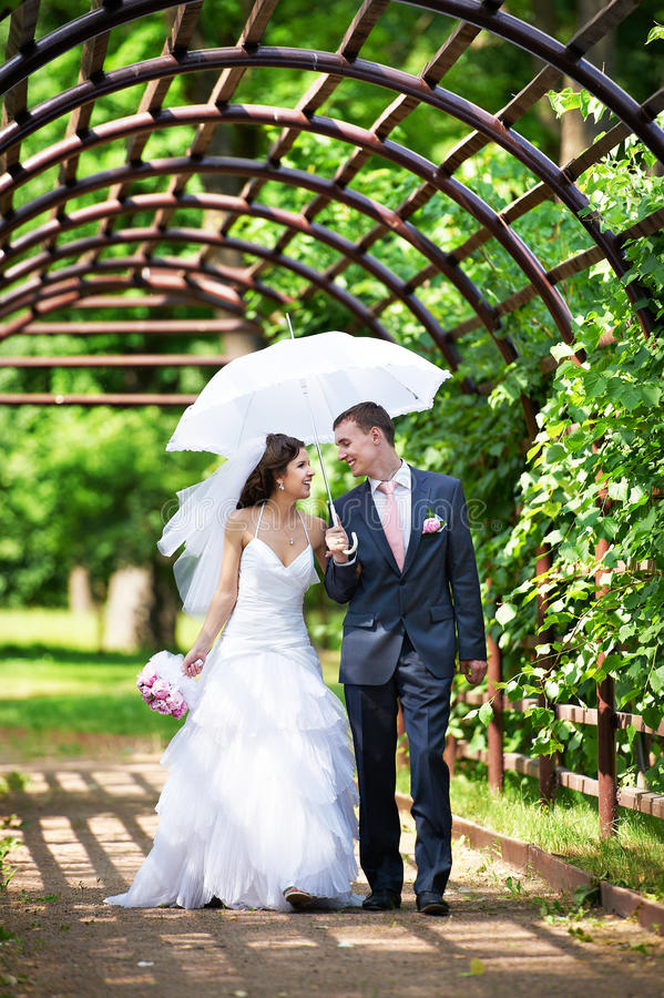 Happy bride and groom goes along the arch stock photo