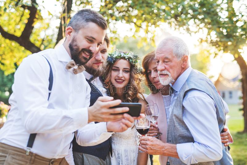 Bride, groom and guests with smartphones taking selfie outside at wedding reception. royalty free stock photos