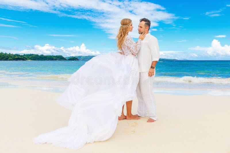 Happy bride and groom having fun on a tropical beach. Wedding an royalty free stock photos