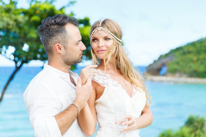 Happy bride and groom having fun on a tropical beach. Wedding an stock image