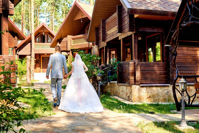 Happy bride and groom holding hands and walking near wooden house in park on wedding day, copy space. Wedding couple in love. Newlyweds, free space royalty free stock photos