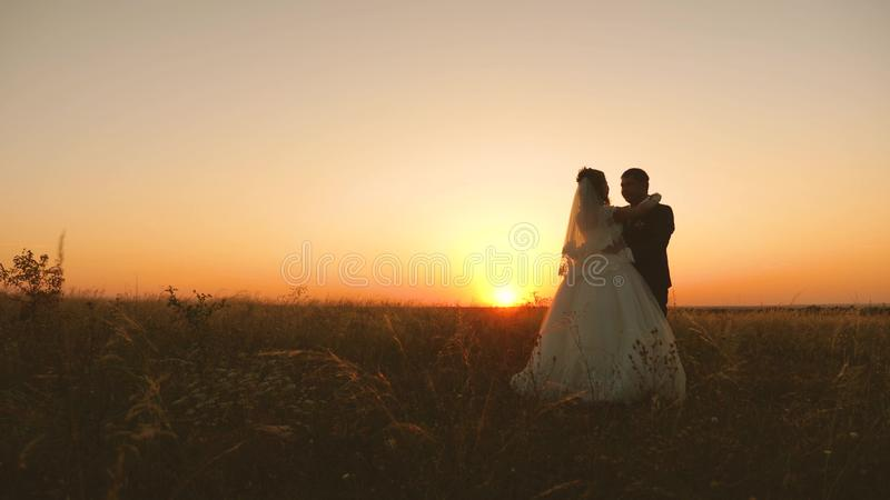 Happy bride and groom hug in the bright sunshine. enamored newlyweds hug each other and stand in the field against the stock photo