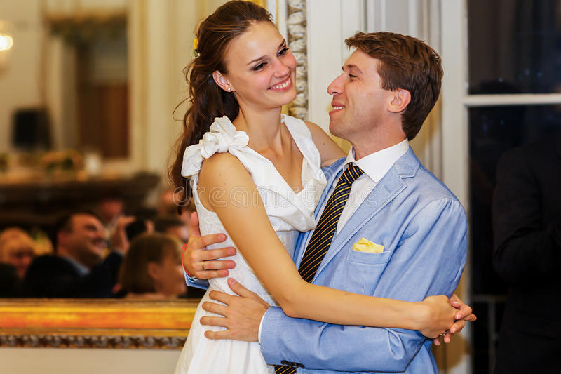 Happy bride and groom hugging smiling look et each other in a stock photos