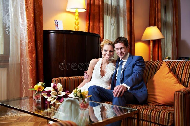 Happy bride and groom in interior of hotel room stock photo