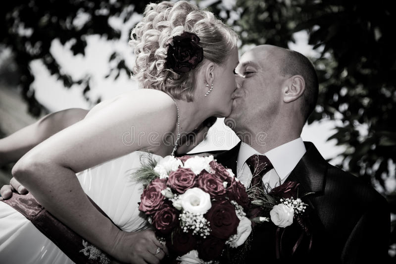 Happy bride and groom kissing. Outdoors royalty free stock photography