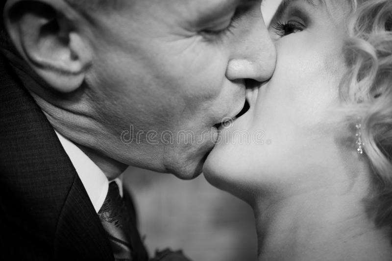 Happy bride and groom kissing. Black and white stock photography