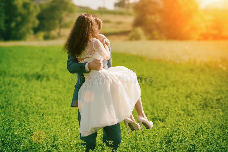 Happy bride and groom kissing in a meadow stock photo