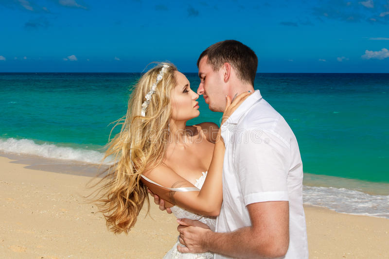 Happy bride and groom kissing on a tropical beach. Blue sea in t royalty free stock images