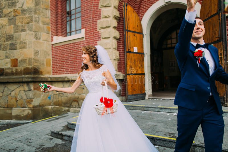Download Happy Bride And Groom Leaving The Church After A Traditional Wedding Ceremony Stock Photo