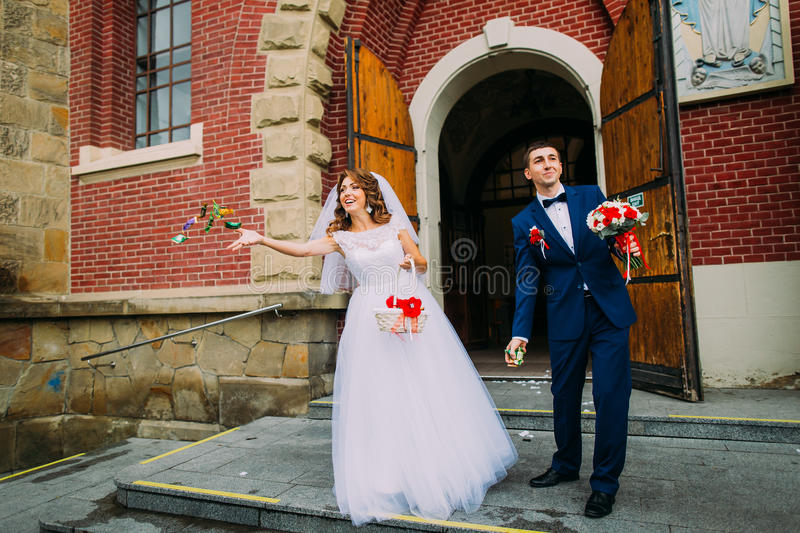Happy bride and groom leaving the church after a wedding ceremony stock photos