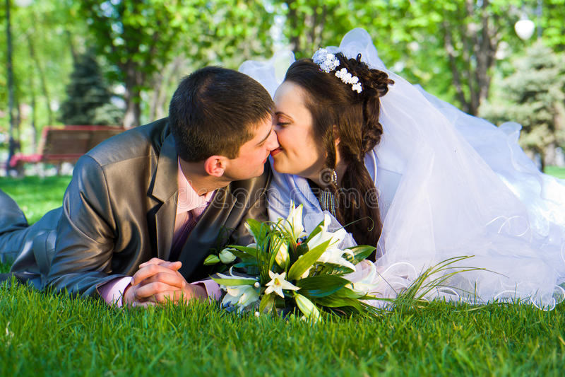 Happy bride and groom lying on grass stock photo