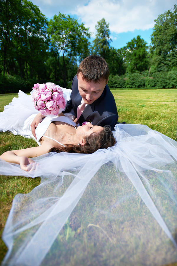 Happy bride and groom lying on grass royalty free stock photos