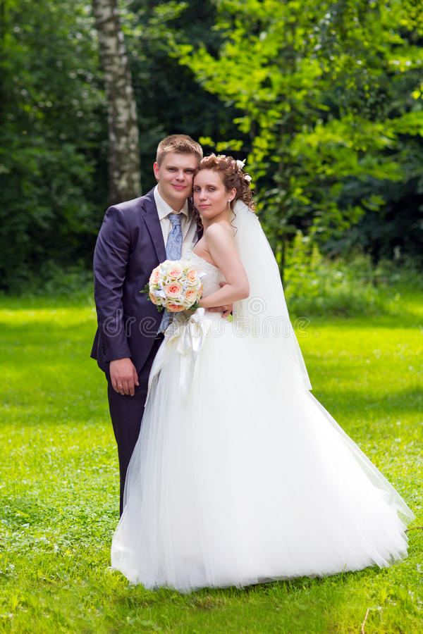 Happy bride and groom in nature. Portrait young happy bride and groom in nature royalty free stock images