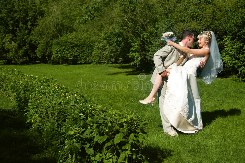 Happy bride and groom in the park royalty free stock photography