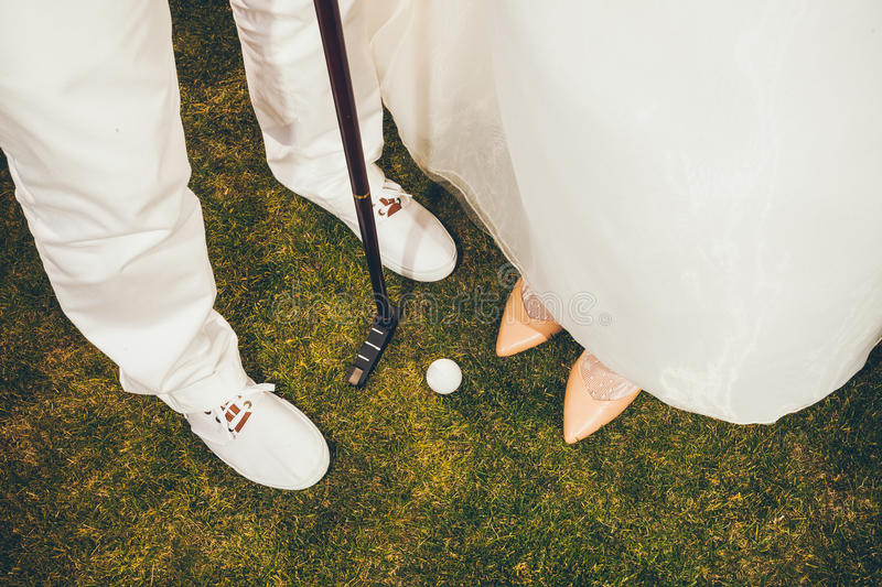 Happy Bride and Groom playing golf - Close up wedding royalty free stock photo