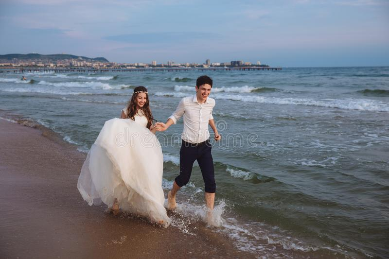 Happy bride and groom run along ocean shore. Newlyweds having fun at wedding day on tropical beach stock photography