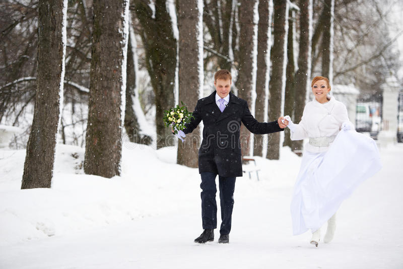 Happy bride and groom running in winter park stock photo