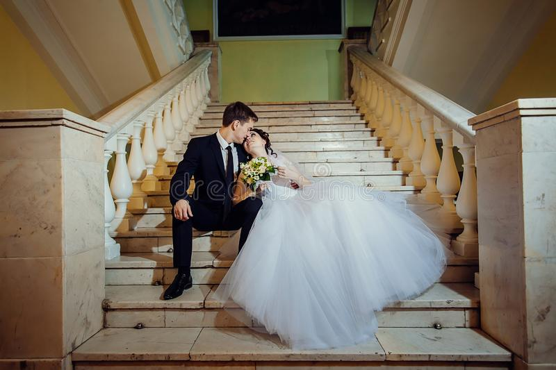 Happy bride and groom are sitting on a white marble staircase, holding hands and looking into each other`s eyes royalty free stock images